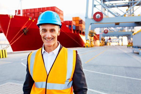 Portrait eines seniorigen Mannes mit Schutzkleidung und Helm vor einem großen Containerschiff am Dock.